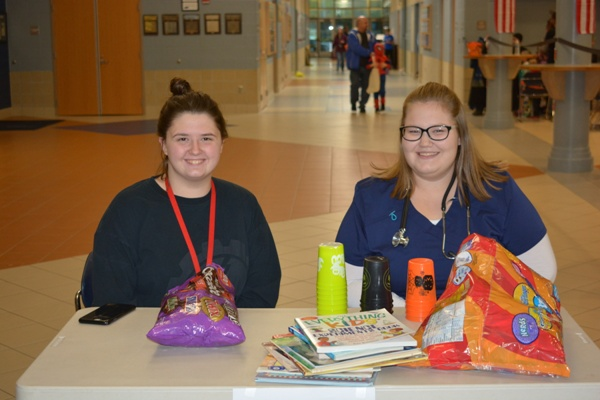 Senior Mackenzie Grope poses with Sydney Miller Snyder as they collect books during the 1st annual SADD NHS Trick or Treat